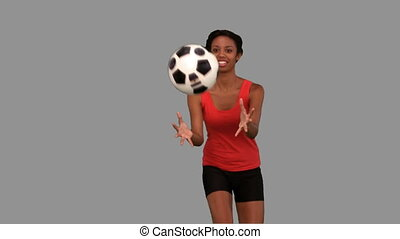 Woman catching a football on grey screen in slow motion