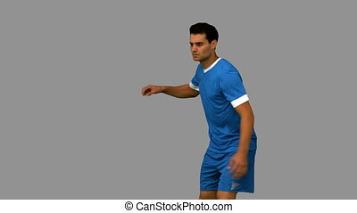 Football player kicking a football on grey screen in slow...