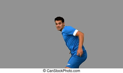 Handsome football player warming up on grey screen in slow...