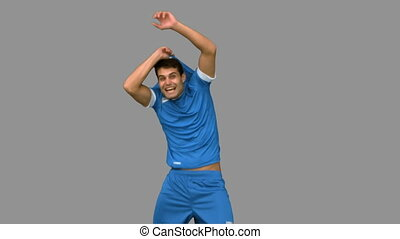 Cheerful football player celebrating a goal on grey screen...