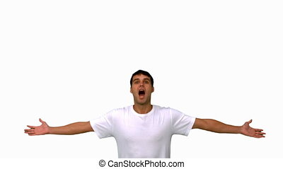 Handsome man jumping and raising arms on white screen in...