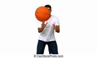 Handsome man playing with a basketball on white screen in...