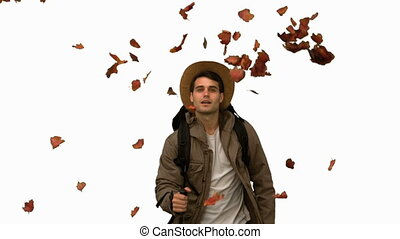 Man walking under leaves falling on white screen in slow...