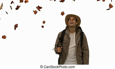Cheerful man standing under leaves falling on white screen...