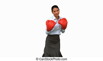 Businesswoman wearing boxing gloves and hitting on white...