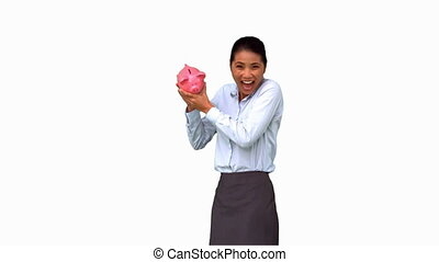 Businesswoman shaking a full piggy bank on white screen in...