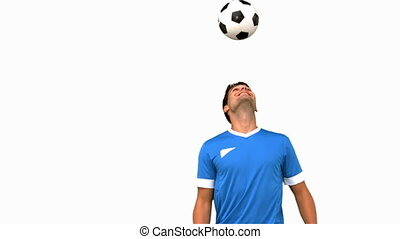 Man juggling a football with his head on white screen