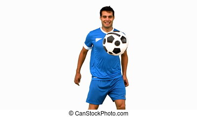 Handsome man juggling a football on white screen