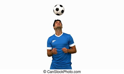Man juggling a football with head on white screen in slow...