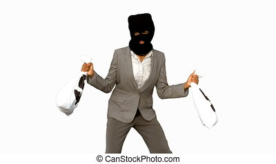 Burglar wearing balaclava and holding money bags on white...