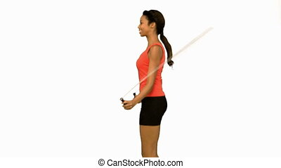 Pretty woman working out with a rope on white screen in slow...