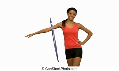 Woman working out with a hula hoop on white screen in slow...