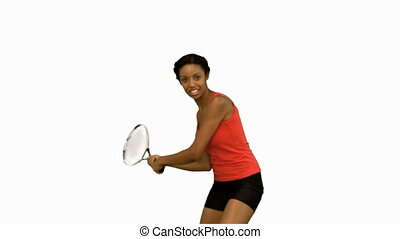 Pretty woman playing tennis on white screen in slow motion