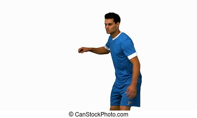 Football player kicking a football on white screen in slow...