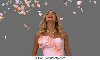 Woman in ballgown standing under petals falling on grey...