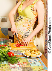 pregnant woman s hands and belly cutting on kitchen with healthy food The concept of food and a healthy lifestyle