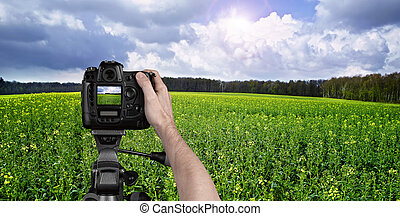Man photographing landscape with digital camera