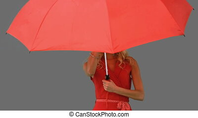 Woman holding an umbrella on grey screen in slow motion