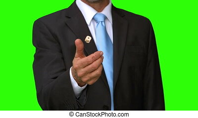 Businessman throwing a die in the air on green screen in...