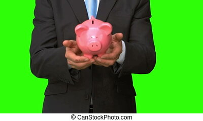 Businessman throwing a piggy bank on green screen in slow...