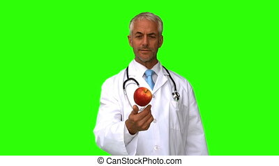 Doctor throwing an apple on green screen