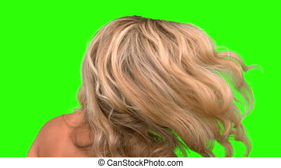 Attractive woman tossing her hair on green screen in slow...