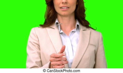 Businesswoman throwing a coin on green screen in slow motion