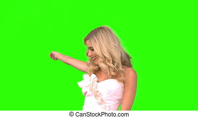 Attractive woman dancing in wedding gown on green screen in...