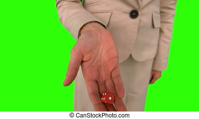 Businesswoman throwing a die on green screen in slow motion