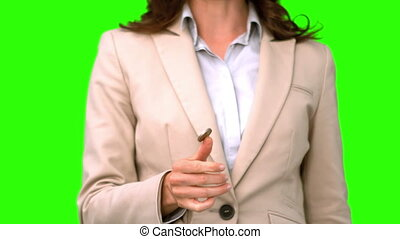 Pretty businesswoman throwing a coin on green screen in slow...