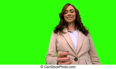 Businesswoman throwing a coin in the air on green screen in...