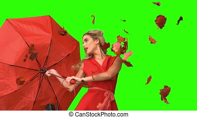 Pretty glamour woman holding a broken umbrella on green...