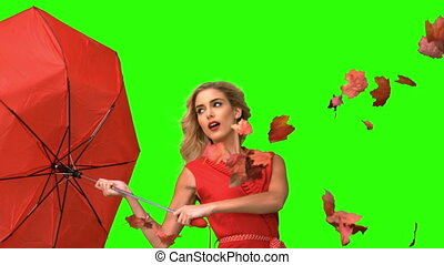 Pretty woman holding a broken umbrella on green screen in...