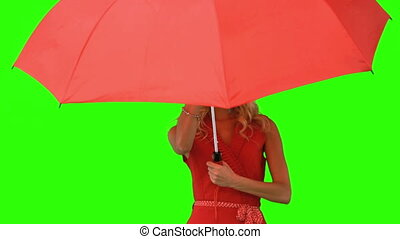 Woman holding an umbrella on green screen in slow motion