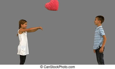 Siblings playing with a heart shaped cushion on grey screen...