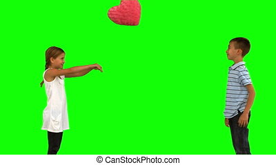 Siblings playing with a heart shaped cushion on green screen...