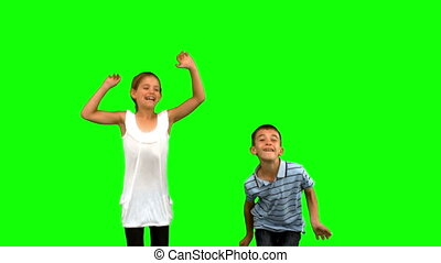 Siblings jumping together on green