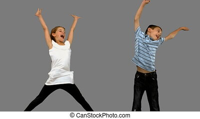 Brother and sister jumping together on grey screen in slow...