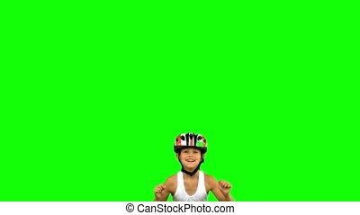 Cute girl wearing a bike helmet and jumping on green screen...