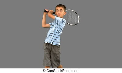 Little boy playing tennis on grey screen in slow motion