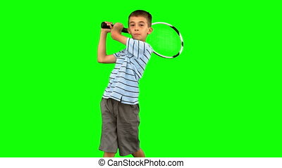 Little boy playing tennis on green screen in slow motion