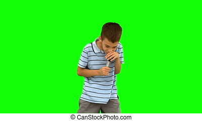 Little boy holding a microphone and singing on green screen...