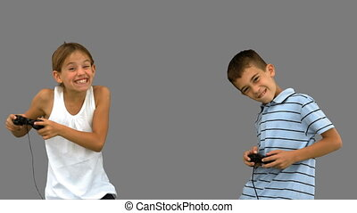 Siblings playing video games on grey screen in slow motion