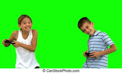 Siblings playing video games on green screen in slow motion