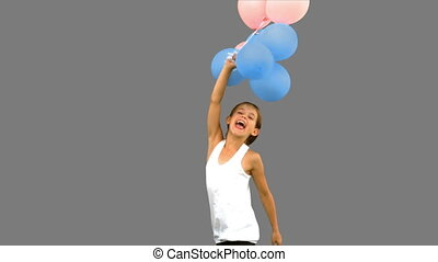 Little girl playing with balloons on grey screen in slow...