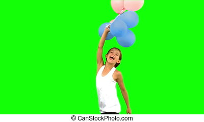 Little girl playing with balloons on green screen in slow...