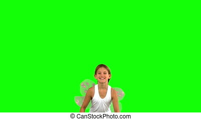 Girl wearing dragonfly wings and jumping on green screen in...