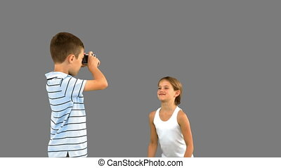 Brother taking pictures of his sister