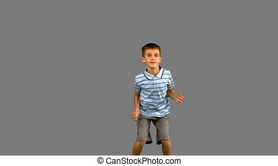 Little boy jumping on grey screen in slow motion