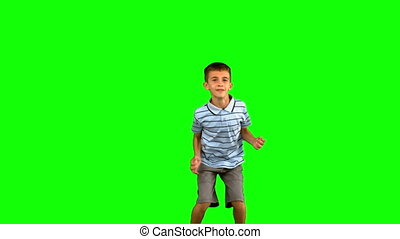 Little boy jumping on green screen in slow motion
